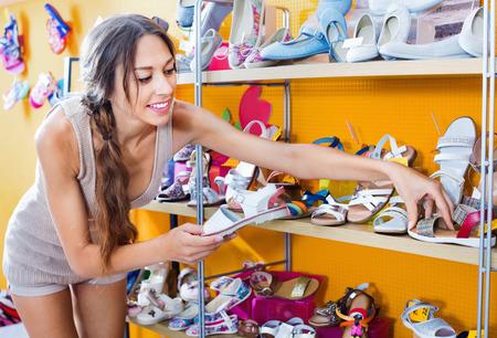 Retrato de una mujer joven que parece confundido con dos pares de zapatos en el departamento de moda Foto de archivo