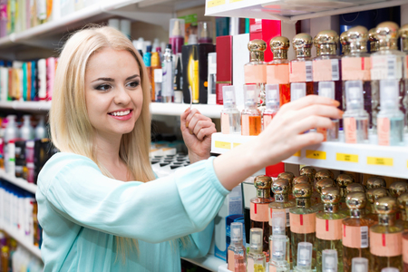 eau de perfume: Cheerful beautiful blond girl buying perfume in fragrance section of supermarket Stock Photo
