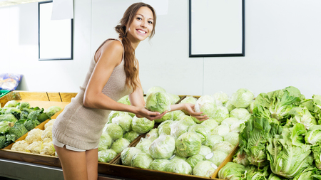 Portrait of young positive woman shopping fresh green lettuce in shop