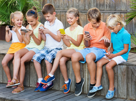 immersed: Busy children holding smartphones in hands and sitting together outdoors Stock Photo