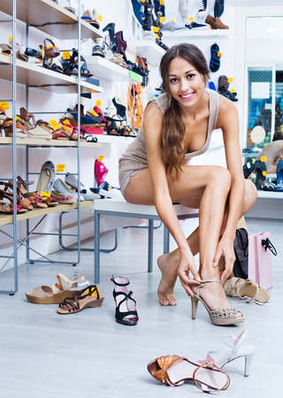 Portrait of  happy positive  woman fitting picked summer footwear in fashion boutique