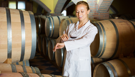laboratorian: Happy young woman in white robe checking ageing process of red wine