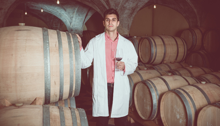laboratorian: Professional taster of winery in uniform posing with wine in cellar