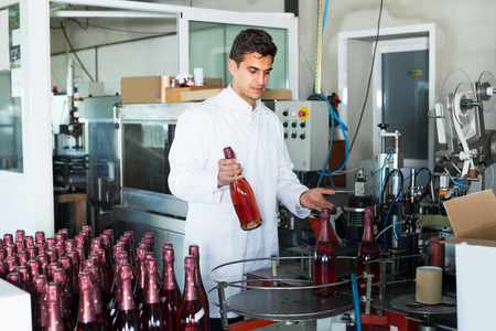 wine register: portrait of professional man in white robe working on wine production on manufactory