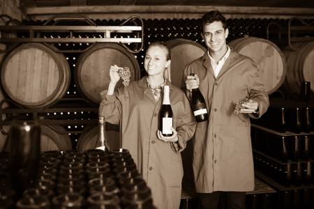 big cork: Two smiling winery employees in uniform holding bottles of wine in aging section in cellar Stock Photo