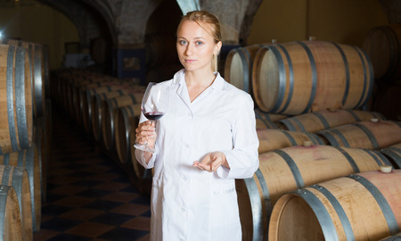 Serious blonde woman in white robe checking ageing process of red wine Stock Photo