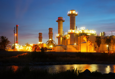 tall chimney: view of  industry plant and river in evening Stock Photo