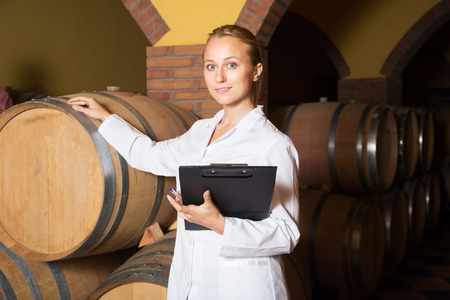 ageing process: Positive blonde woman in white robe checking ageing process of red wine