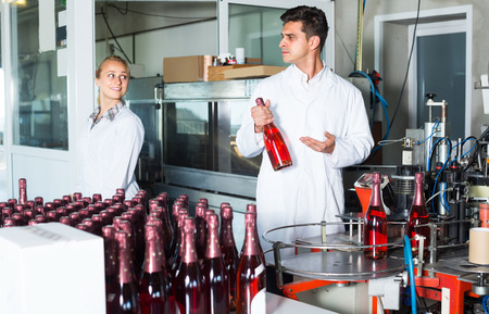 man and woman colleagues in white robes working on wine packaging on wine manufactory. Focus on man Stock Photo