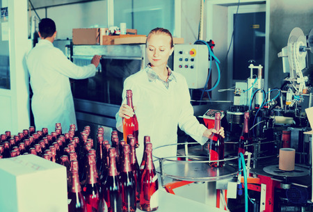 Young smiling  woman employee in coat working on final section of wine production on factory