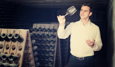 proficient: Proficient concentrated man holding glass of wine in cellar on winery factory
