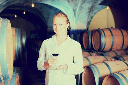 taster: Beautiful female wine house worker checking quality of product in cellar