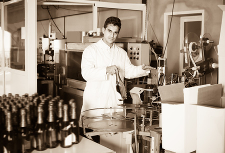 wine register: Man holding newly produced bottle of wine on winery manufactory