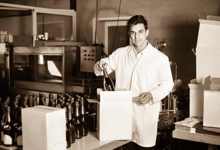 diligente: hombre diligente positivo contenta en el abrigo de pie en la sección de embalaje en la fábrica de elaboración del vino Foto de archivo