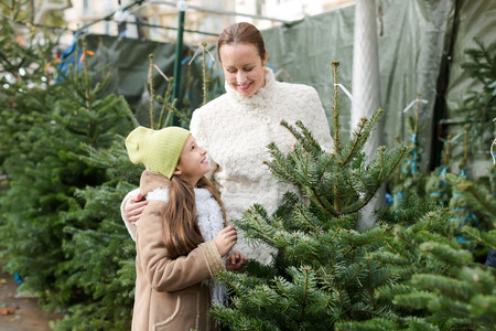 Happy smiling mother and daughter staying at market among Christmas trees. Focus on girl