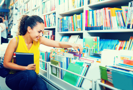 publishers: portrait of attractive young woman selecting textbooks for school in book shop Stock Photo