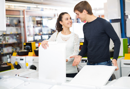 lavadora con ropa: family couple buying new clothes washer in appliance store