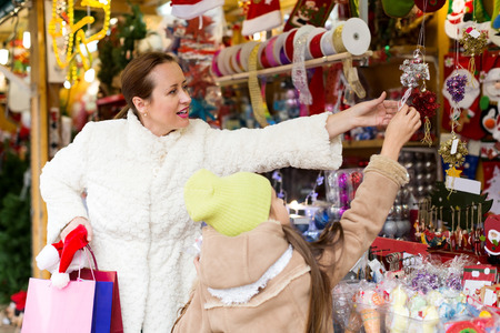 mother with little daughte buying decorations for Christmas. Focus on woman