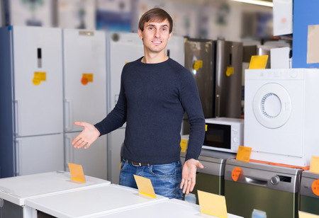 hobs: Portrait of ordinary young man 25s at household appliances store Stock Photo