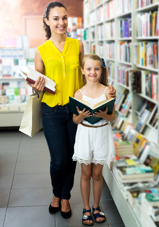 glad: Cheerful glad woman showing open book to girl in school age in book boutique