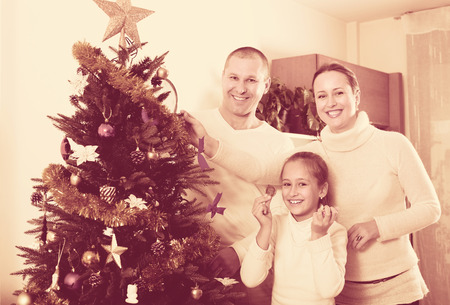 decorating christmas tree: Smiling parents and daughter decorating Christmas tree in the living room at home