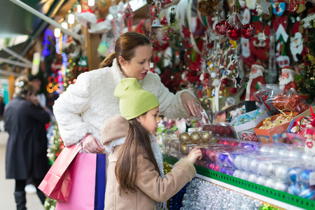 5s: Mother with preschooler daughter choosing home decorations in Christmas market. Focus on girl