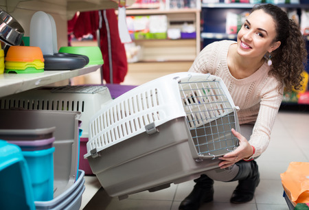 petshop: Smiling young female customer buying kennel for pet in shop Stock Photo