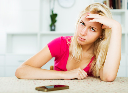 Portrait of young irritated woman waiting for call sitting indoors Stock Photo