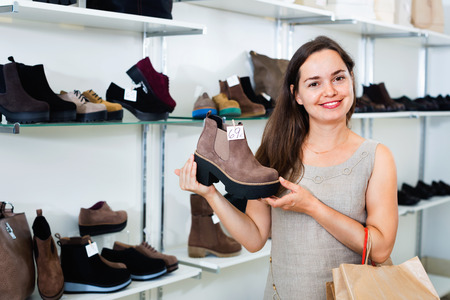 brogues: Young  positive woman choosing fall boots in shoes store and smiling