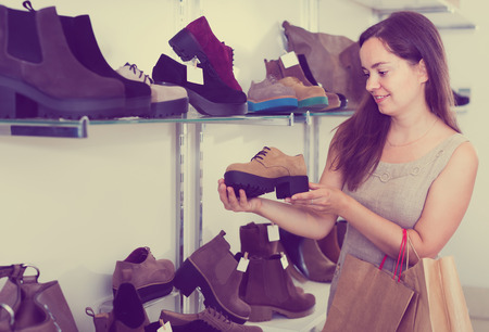 footgear: Portrait of laughing woman selecting loafers in footgear center Stock Photo