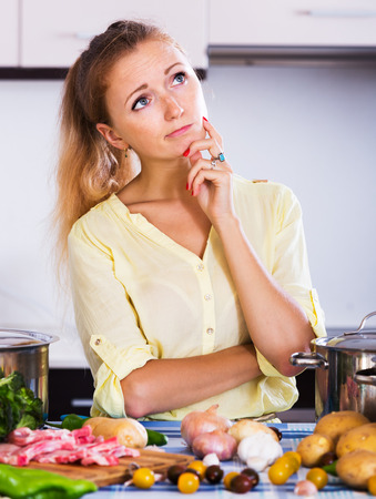 Unhappy woman with meat and vegetables at kitchen table Stock Photo
