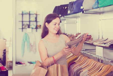 footgear: Portrait of young female customer selecting shoes in footgear center Stock Photo