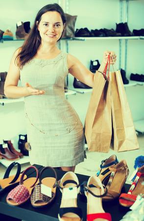 footgear: Portrait of positive female selecting shoes in footgear store Stock Photo