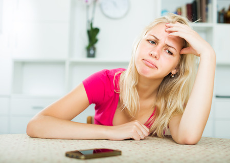Blond woman looking annoyed and waiting for call on mobile phone indoors Stock Photo