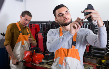 toiling: Two repairmen toiling in locksmiths workshop Stock Photo