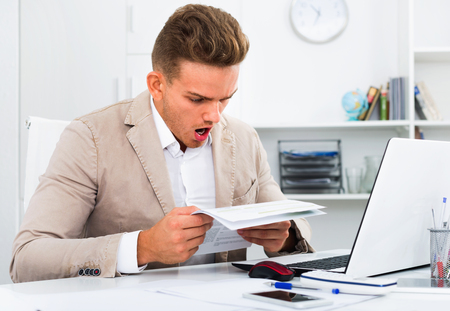 Upset sad young man having business problems with documents at workplace