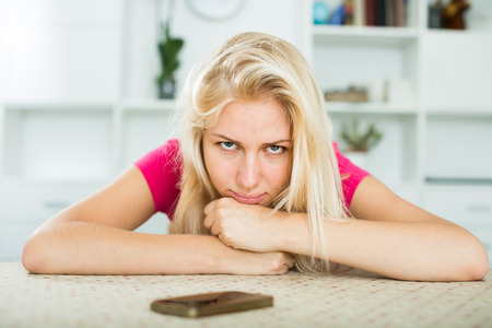 Closeup portrait of young sad girl waiting for call at home
