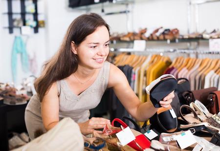 footgear: Portrait of joyful young female customer selecting summer  shoes in footgear center Stock Photo
