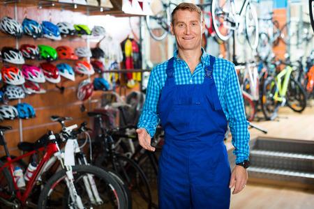 friendly smiling man seller in working uniform standing in bike store