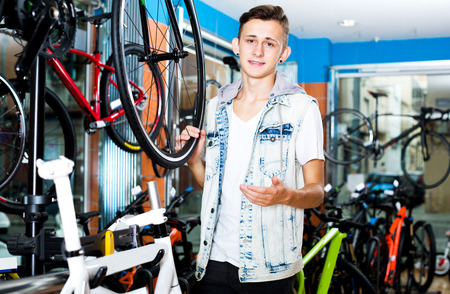 Portrait teenager boy looking for and trying new racing bicycle in sport shop Stock Photo
