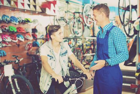 Positive man seller in uniform helping teenage boy choose bicycle in sport store