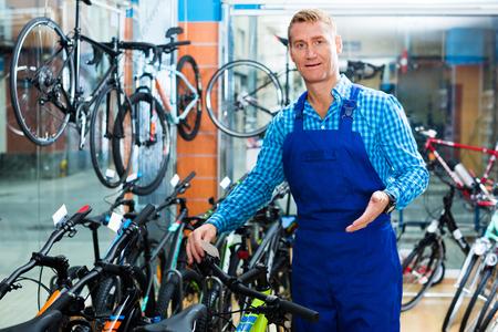 positive man seller wearing uniform standing in bike store