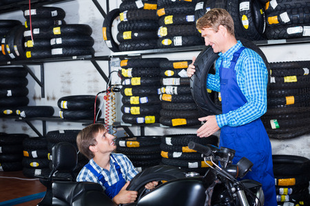 tire fitting: Two happy coworkers mechanics working with new tires in workshop Stock Photo