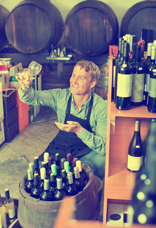promoting: Portrait of male seller in uniform promoting to taste a wine before purchasing it in the cellar