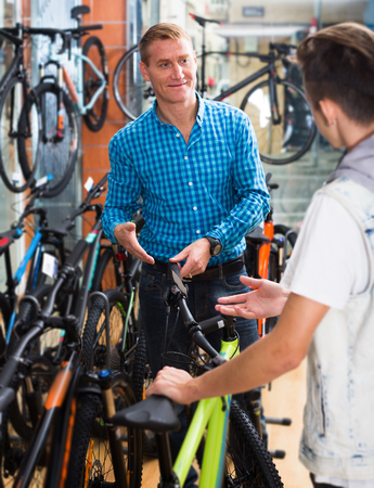 family units: Positive man and boy teenager picking new bicycle in sport hypermarket