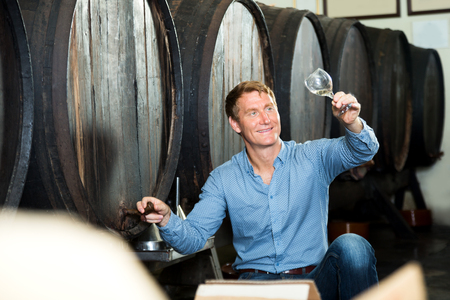 glad: Portrait of glad man tasting wine before purchasing it in winery