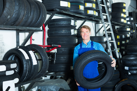 tire fitting: Mature mechanic man standing with new car tires in hands in shop Stock Photo