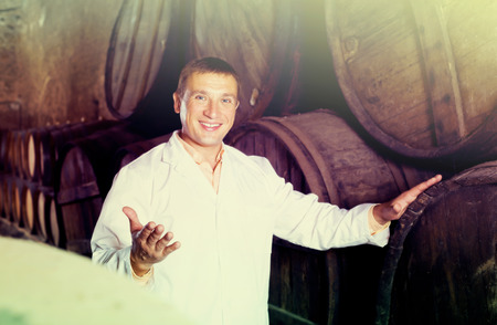laboratorian: Smiling worker of winery posing with wine barrels in cellar