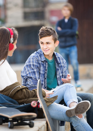 unfaithfulness: Jealous teen and his smiling american friends after conflict outdoors