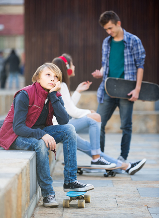 Jealous american teen and his friends after conflict outdoors